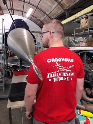 Steve, l'un des membres des Ailes anciennes de Haute-Savoie, pose avec le t-shirt de l'association toulousaine, le 30 mai à Excenevex.