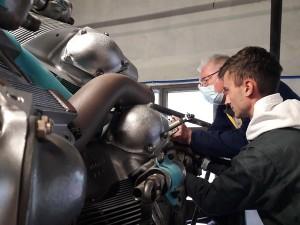 """Killyan et Gérard, lors du remontage d'une pompe du moteur de 18 cylindres Wright R-3350 """"Cylcone"""", le 6 juin."""